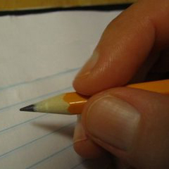 hand holding pencil while writing